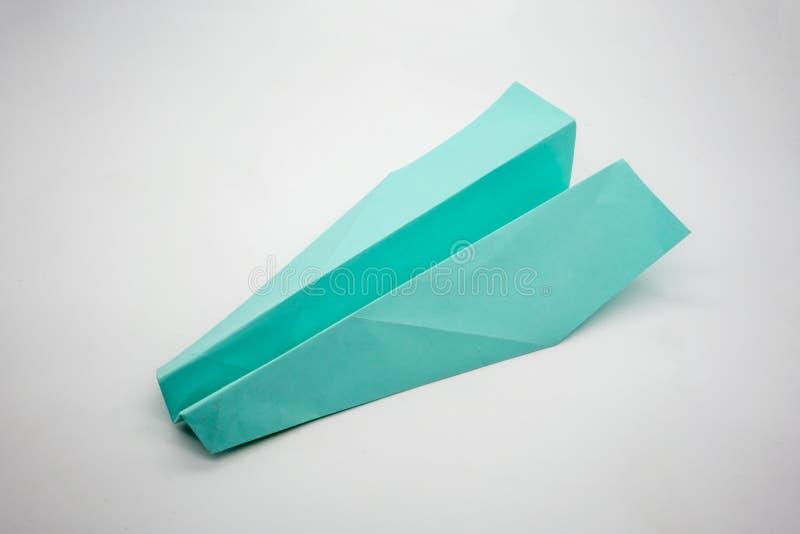 Lichtblauw groen die origamidocument vliegtuig op witte achtergrond wordt geïsoleerd stock afbeeldingen