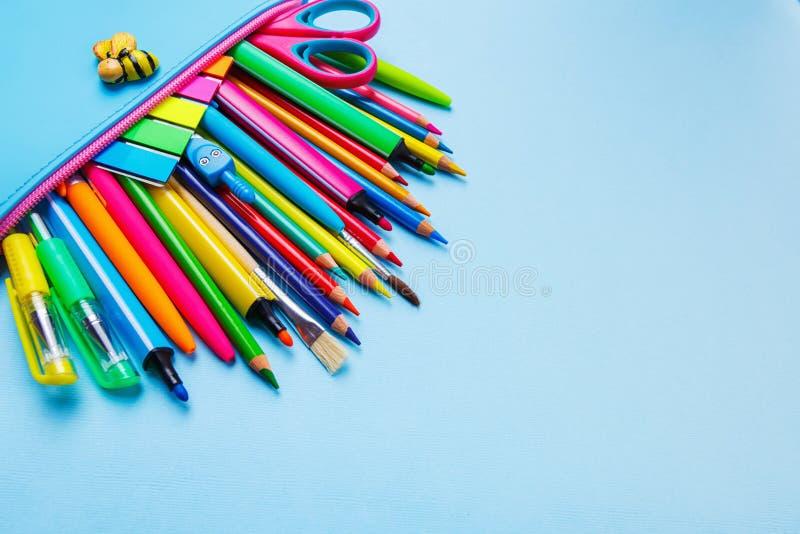 Lichtblauw potloodgeval met een rode ster en een gekleurde kantoorbehoeften op een blauwe achtergrond stock afbeelding