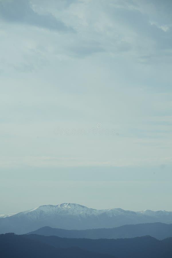 Lichtblauwe hemel met wolken over sneeuwbergenlandschap stock afbeelding