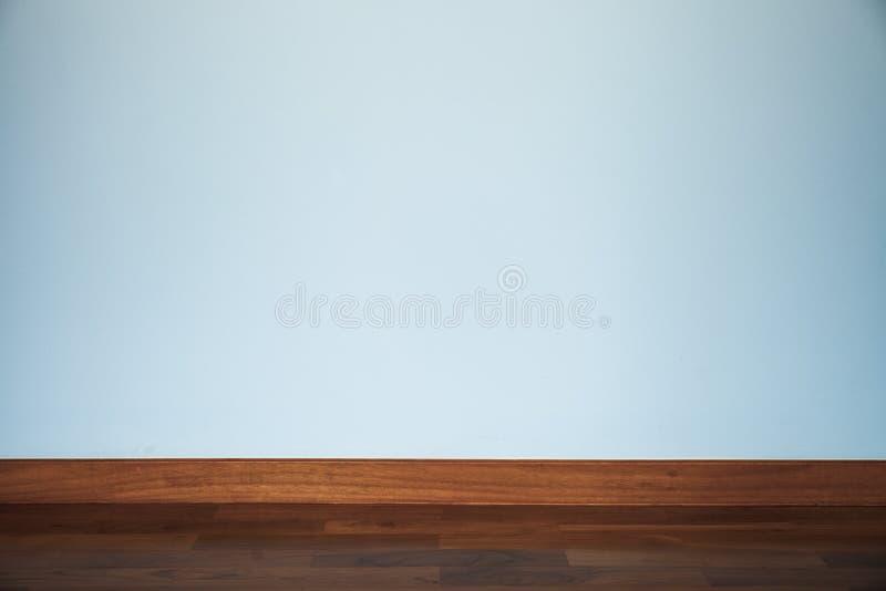 Lichtblauwe muur met houten vloer stock foto's