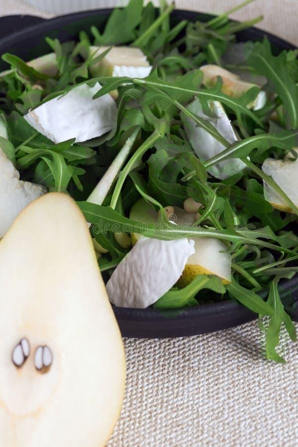 Lichte de zomersalade met peer Ingredi?nten: arugula, peer, Briekaas, pijnboomnoten, honingssaus recept Juiste voeding Gezond stock foto
