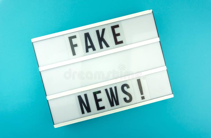 Lichte doos met het krantekop Valse Nieuws met tegen blauwe achtergrond, blogconcept stock fotografie