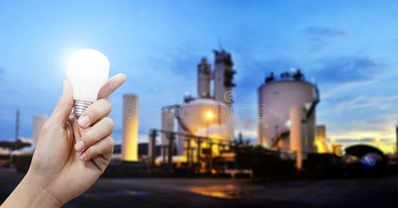 Lichte energie voor industrie, Hand die gloeilamp in industrieel onderwerp de houden stock foto