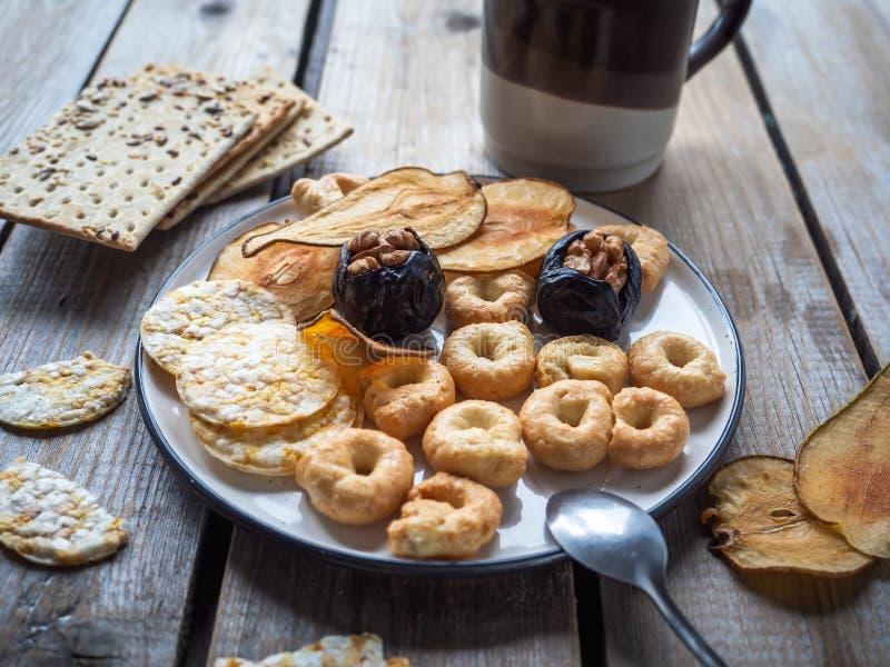 Lichte lunch met thee in ceramische en korrelkoekjes, gedroogd fruitspaanders in een kleine ronde plaat op een houten rustieke di stock afbeeldingen