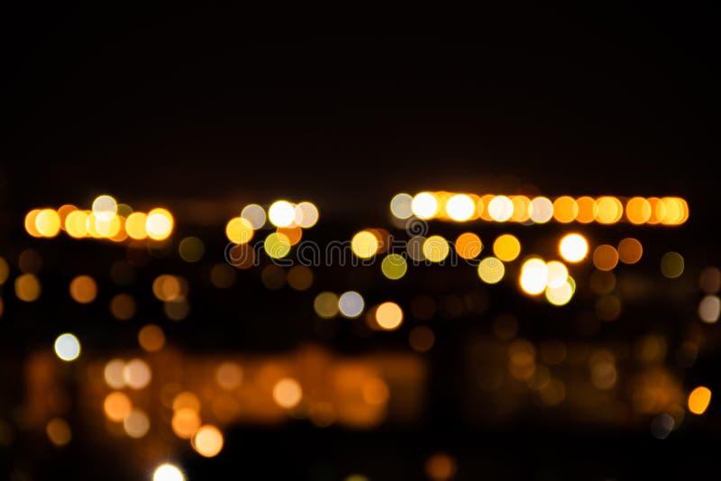 Lichte nacht bij de abstracte achtergrond van het stads bokeh onduidelijke beeld De kleurrijke donkerblauwe hemelnadruk wijst glo royalty-vrije stock fotografie