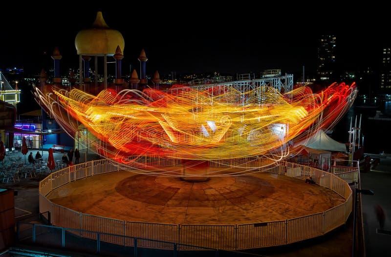 Lichte slepen van een funfairrit bij nacht stock afbeelding