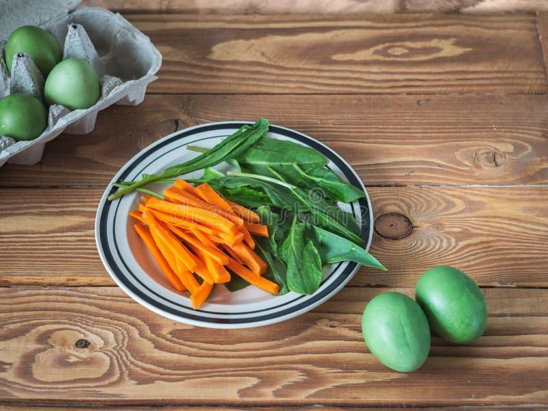 Lichte snack van gehakte wortelen en verse zuring op een ronde plaat, in de achtergrond groene geschilderde kippeneieren op houte royalty-vrije stock foto's