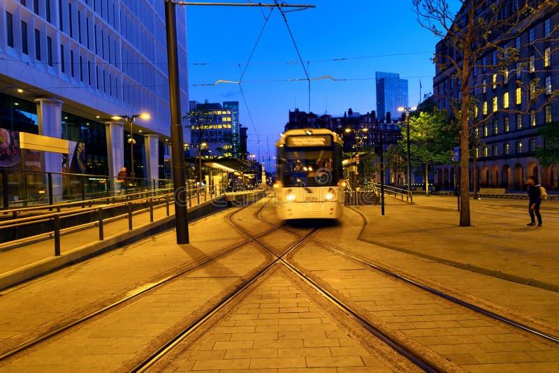 Lichte spoor gele tram in het stadscentrum van Manchester, het UK in de avond stock afbeeldingen