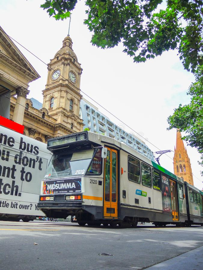 Lichte spoortram die een straat van Melbourne de stad in dichtbij de Stadhuisbouw doornemen stock foto's