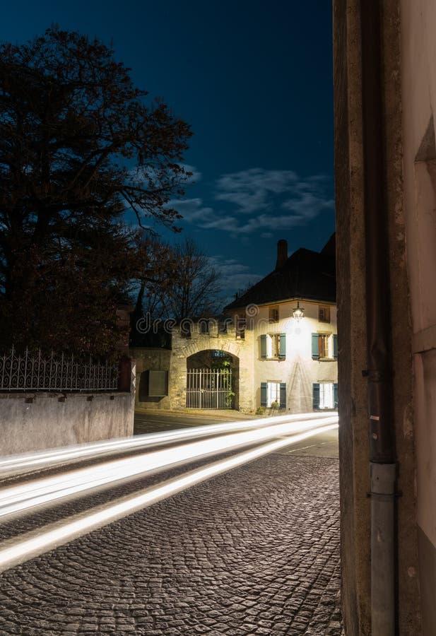 Lichte stroken van auto's die door een smalle dorpsstraat overgaan met oude huizen onder een volle maanhemel op de achtergrond stock fotografie
