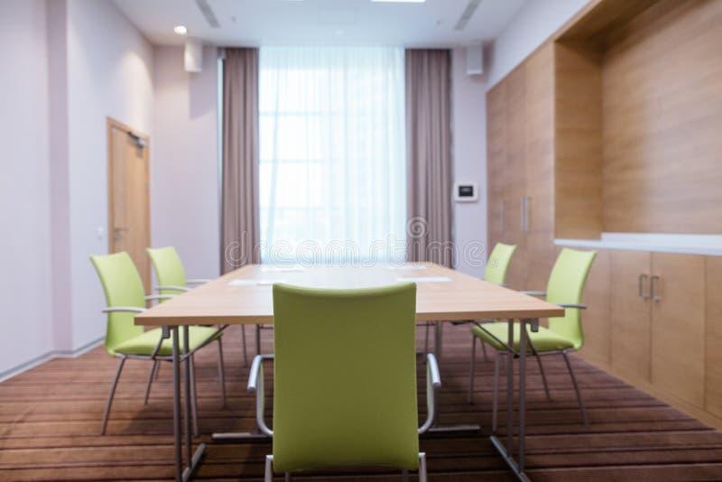 Lichte vergaderzaal met douane-bouwstijl meubilair, bruine gordijnen en wit Tulle royalty-vrije stock fotografie
