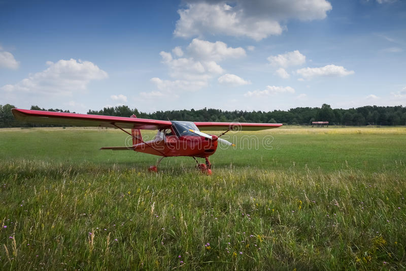 Lichte vliegtuigen Lichtrood schoolvliegtuig op luchthavengras stock fotografie