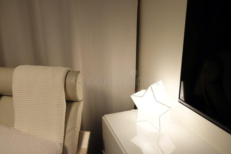 Lichte zachte leunstoel met plaid, hoog achterlezingslamp boven het hoofd stock afbeelding