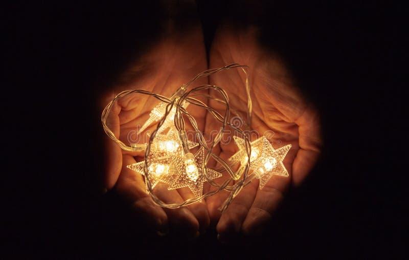 Lichten in de palmen De handen die van vrouwen een slinger, warme Kerstmisstemming, zachte nadruk houden royalty-vrije stock afbeeldingen