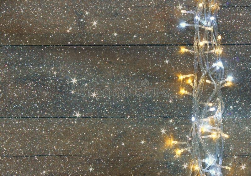 Lichten van de Kerstmis de warme gouden slinger op houten rustieke achtergrond het gefiltreerde beeld met schittert bekleding stock afbeeldingen