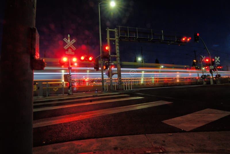 Lichter von einem Nahverkehrszug gehen, durch ein Straßenbild als Nachtfälle zu streifen lizenzfreie stockfotografie