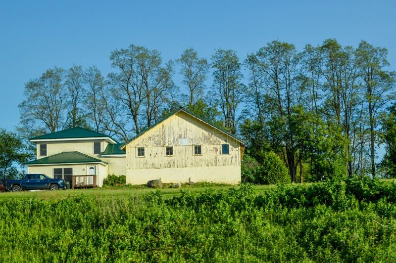 Lichtgeel huis en Barn met een Blue Truck royalty-vrije stock afbeeldingen