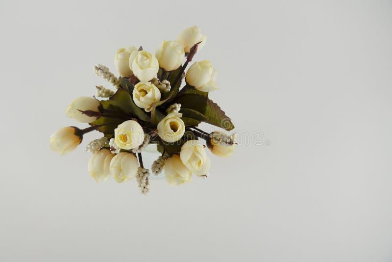 Lichtgele plastic bloemen in een glasvaas royalty-vrije stock afbeelding