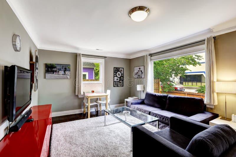 Lichtgrijze woonkamer met helder rood kabinet en zwarte furnitu stock afbeelding