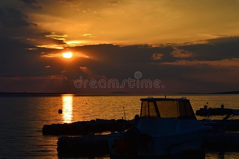Lichtjes bewolkte zonsondergang boven het strand van Vrsi Mulo met lijn van zichtbare molos, boten en silhouet van visser stock fotografie