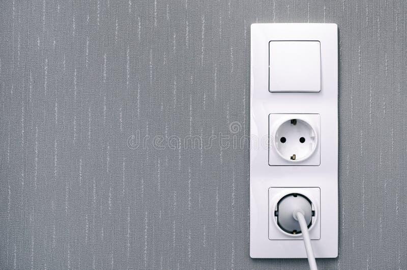 Lichtschalter, Netzdosen, führen und verstopfen auf grauer Wand stockbilder