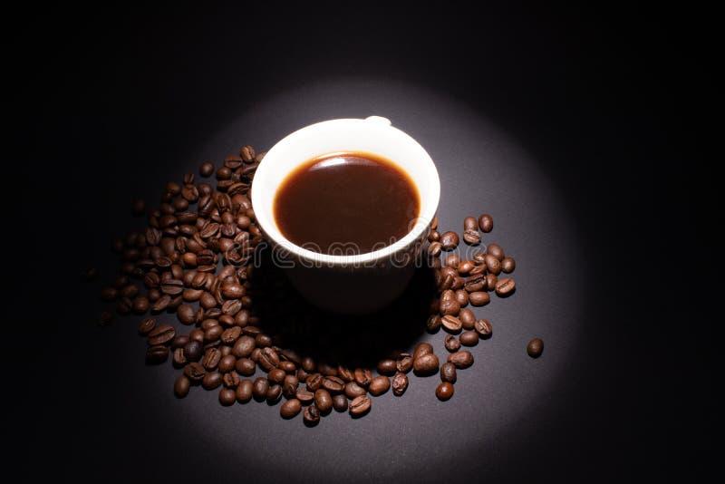 Lichtstraal op eiwitkoffieemmer met een drank in koffiebonen op een donkere achtergrond royalty-vrije stock afbeelding