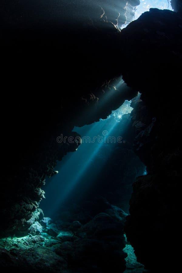 Lichtstralen en Onderwaterhol in Solomon Islands stock afbeeldingen