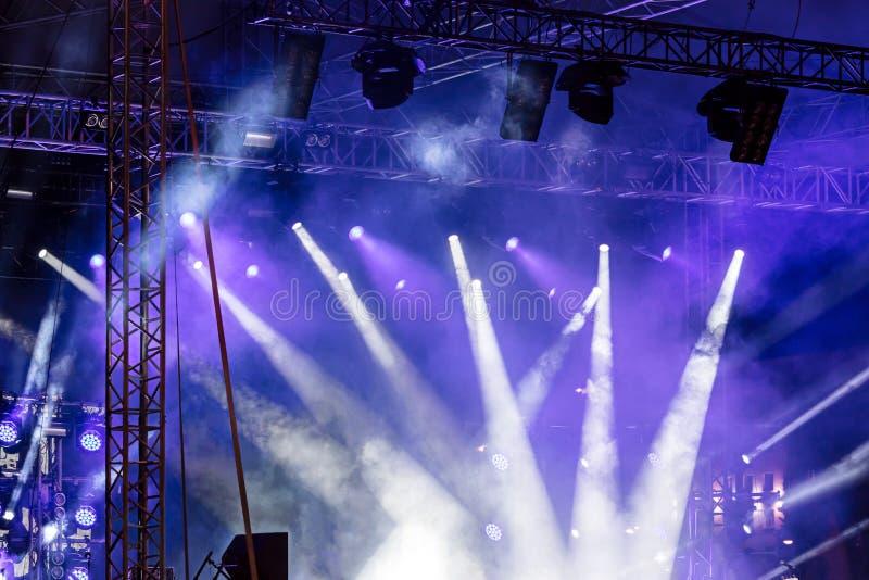 Lichtstralen op stadium heldere schijnwerpers die neer glanzen blauw mannetje stock afbeelding