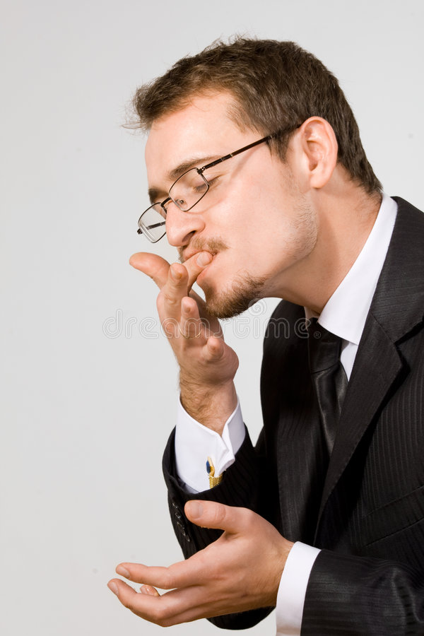 Licking fingers good. Young handsome businessman licking fingers stock image