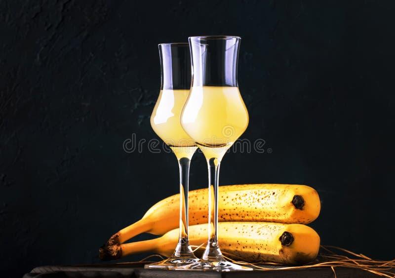 Licor amarillo del plátano en vasos de medida y plátanos maduros frescos en la tabla en fondo azul marino imagenes de archivo