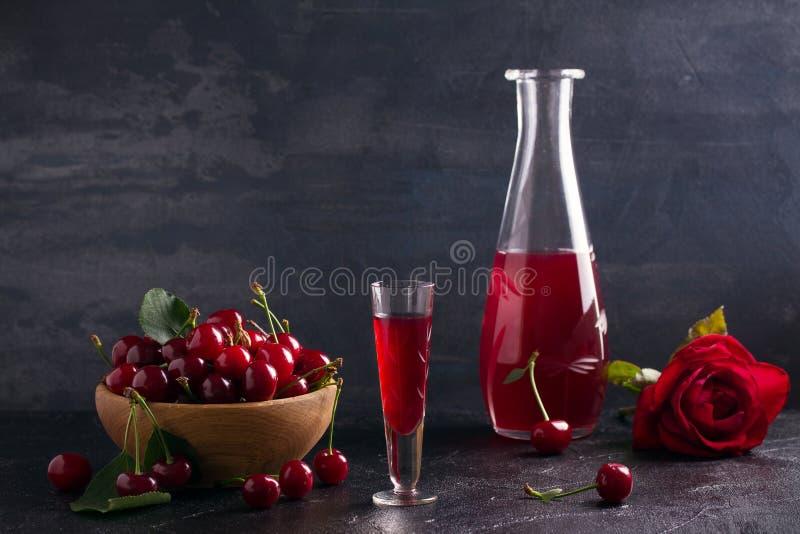 Licor caseiro da bebida do álcool da cereja com as bagas frescas da cereja fotos de stock royalty free