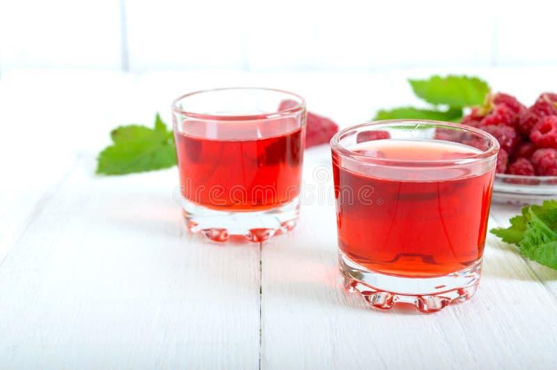 Licor de la frambuesa en las bayas de cristal y frescas en un fondo blanco El alcohólico condimentó la bebida fotografía de archivo libre de regalías