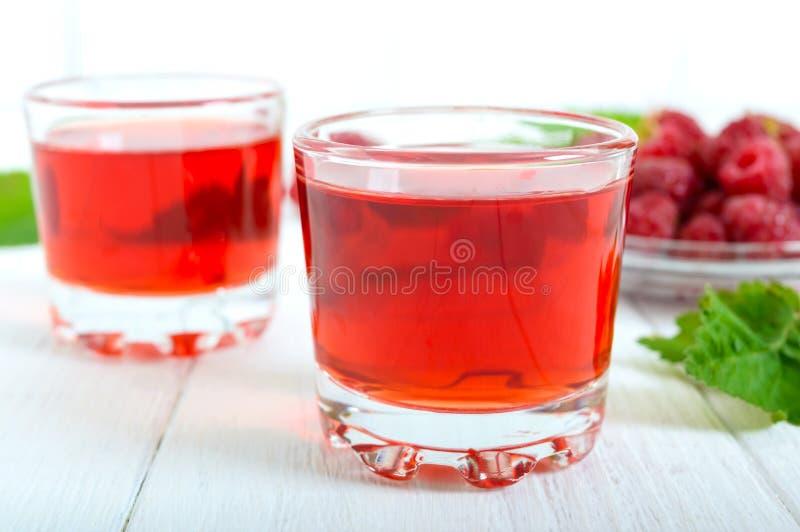 Licor de la frambuesa en las bayas de cristal y frescas en un fondo blanco El alcohólico condimentó la bebida fotos de archivo libres de regalías