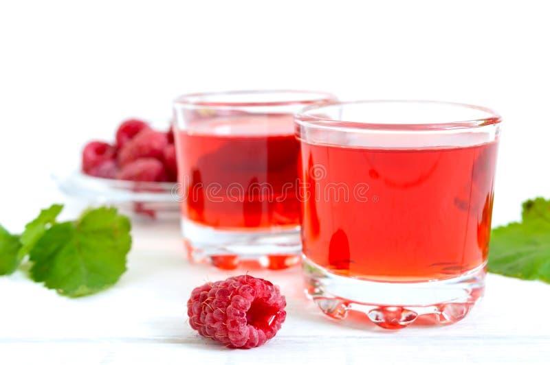 Licor de la frambuesa en las bayas de cristal y frescas en un fondo blanco El alcohólico condimentó la bebida imagen de archivo libre de regalías