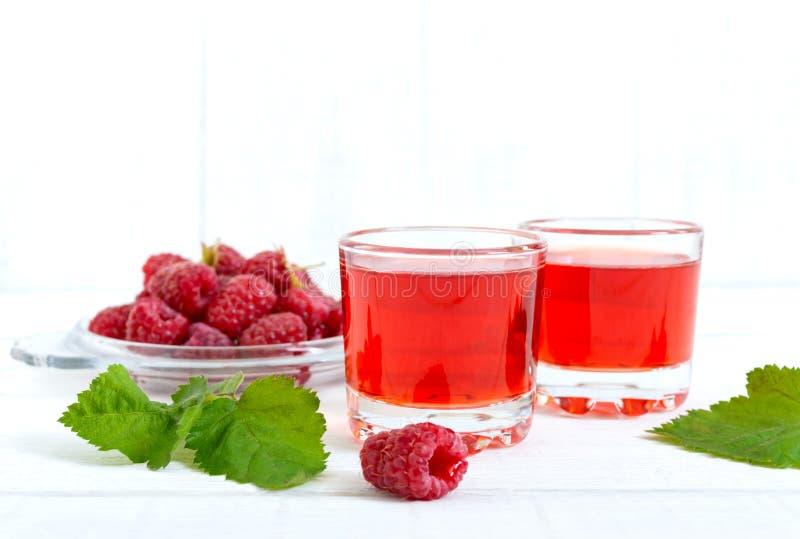 Licor de la frambuesa en las bayas de cristal y frescas en un fondo blanco El alcohólico condimentó la bebida foto de archivo libre de regalías