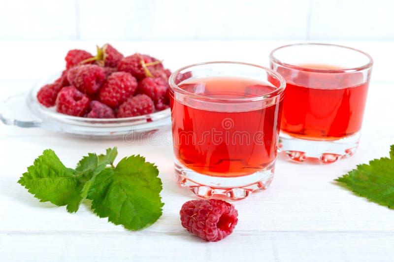 Licor de la frambuesa en las bayas de cristal y frescas en un fondo blanco El alcohólico condimentó la bebida imagen de archivo