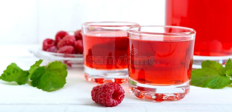 Licor de la frambuesa en las bayas de cristal y frescas en un fondo blanco El alcohólico condimentó la bebida bandera fotografía de archivo