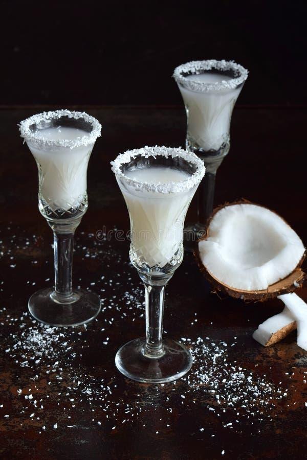 Licor do coco no vidro com cocos quebrados Cocktail delicioso do leite de Pinacolada com rum Licor da bebida do álcool Copie o es imagem de stock royalty free