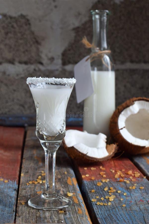 Licor do coco no vidro com cocos quebrados Cocktail delicioso do leite de Pinacolada com rum Licor da bebida do álcool Garrafa de imagens de stock