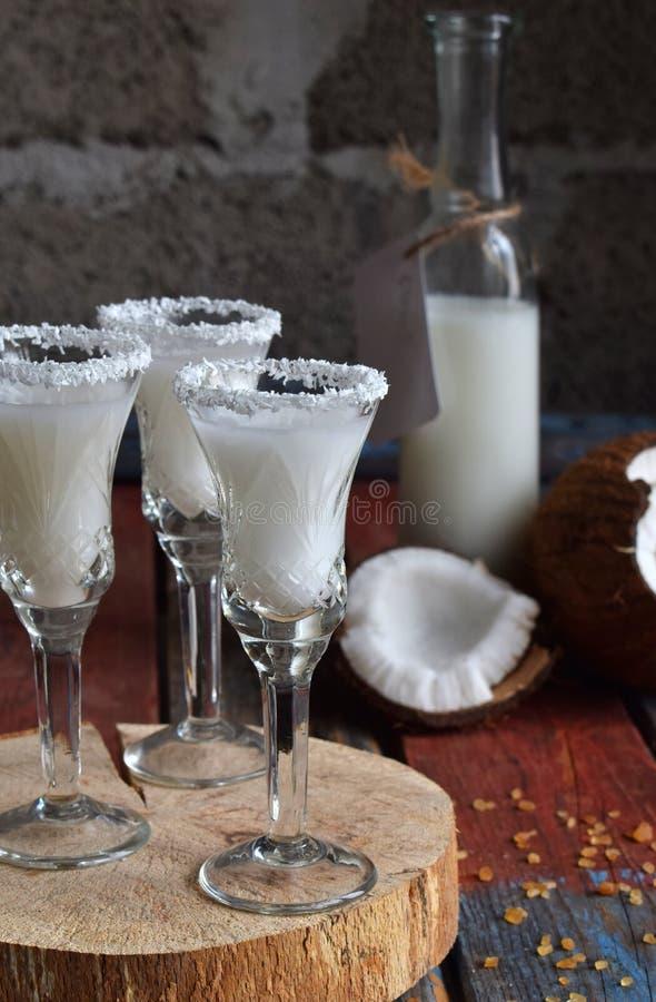 Licor do coco no vidro com cocos quebrados Cocktail delicioso do leite de Pinacolada com rum Licor da bebida do álcool Garrafa de imagem de stock royalty free