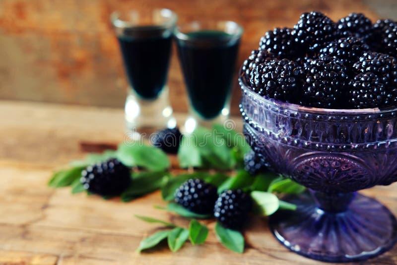 Licor do fruto de Blackberry em dois vidros de tiro com bagas e GR foto de stock