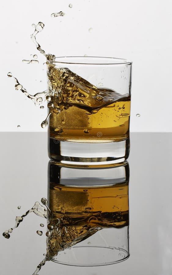 Licor marrom dourado que espirra com o gelo em um vidro fotografia de stock