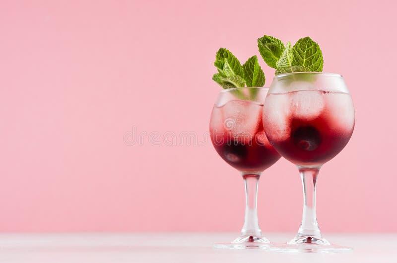 Licores alcoólicos vermelhos árticos excelentes com cubos de gelo, mirtilo, a hortelã verde em dois copos de vinho na tabela d fotografia de stock