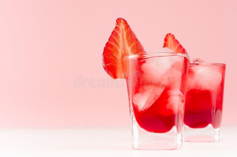 Licores caseiros vermelhos em dois vidros disparados com cubos de gelo, fatia da morango no fundo cor-de-rosa pastel macio e tabe imagens de stock royalty free