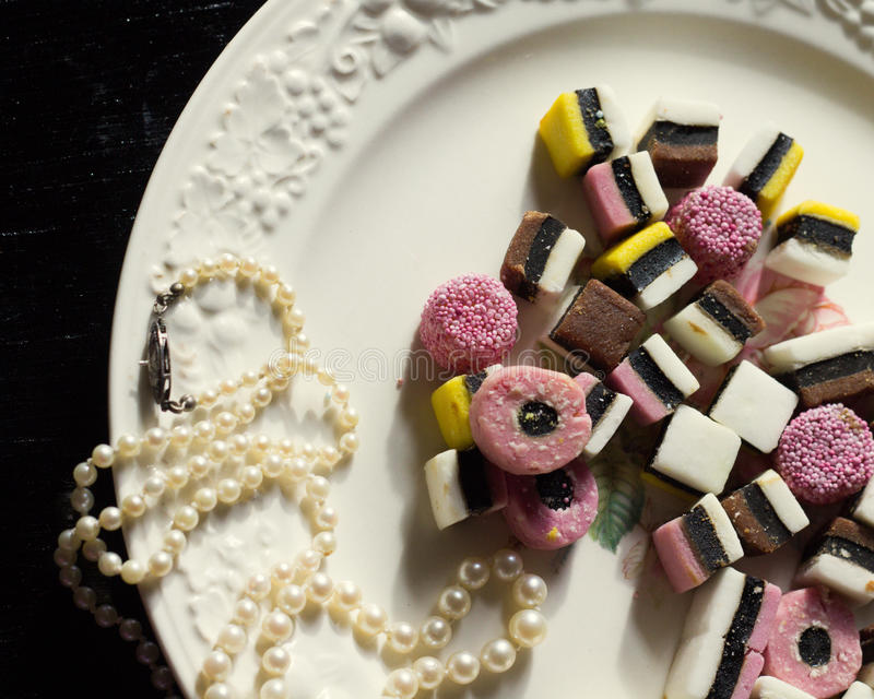 Licorice on a Plate with Pearls royalty free stock images