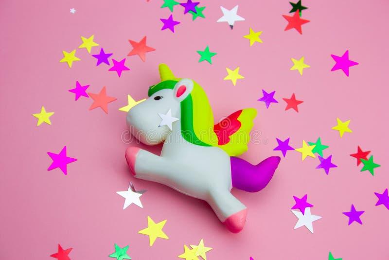 licorne de jouet et scintillements visqueux sous forme d'étoiles sur le fond rose en pastel images stock