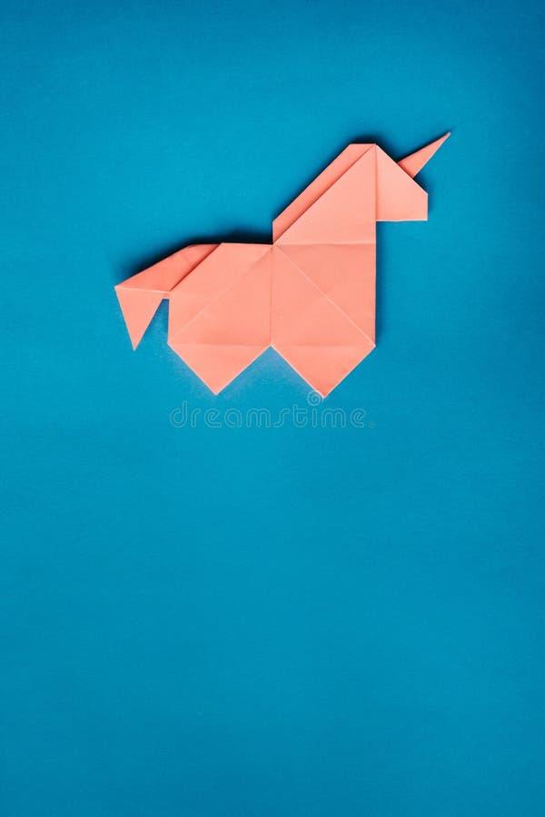 Licorne rose d'origami sur le fond bleu images stock