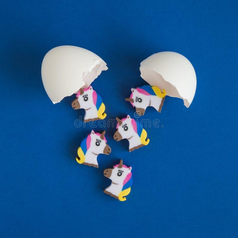 Licornes colorées sortant de l'abrégé sur cassé oeufs photos libres de droits