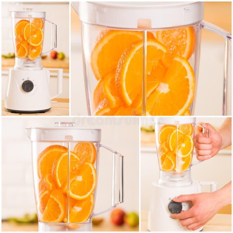 Licuadora blanca con las naranjas jugosas en una tabla de madera imagen de archivo