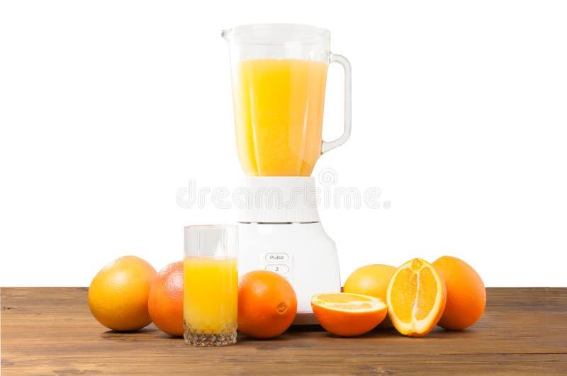 Licuadora con el jugo y las frutas frescas en la tabla en el fondo blanco imagen de archivo libre de regalías